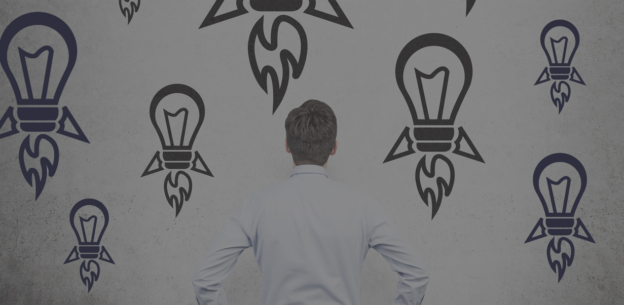 businessman looking to drawing rocket lamp on wall